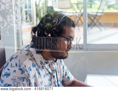 Young, Bearded, Long-haired Latino Man, Sitting Behind Glass With A Headset. New Normal Concept. Sel