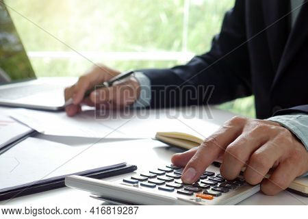 Men Use The Calculator And Take Notes With Calculations About The Expenses At The Office. Prepare To