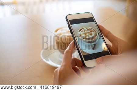 The Hand Of The Woman Using A Smartphone To Take A Picture Of A Coffee In A Cafe To Post On Social M