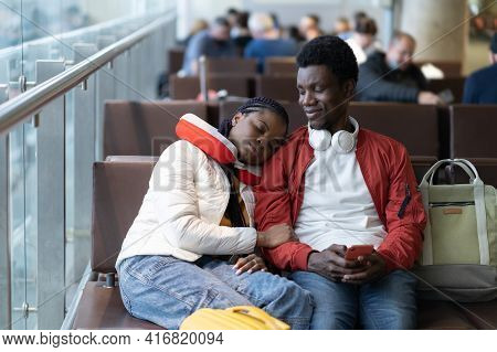 African Couple Of Tourists In Waiting Area Of Airport Terminal Sit And Nap Before Departure And Chec