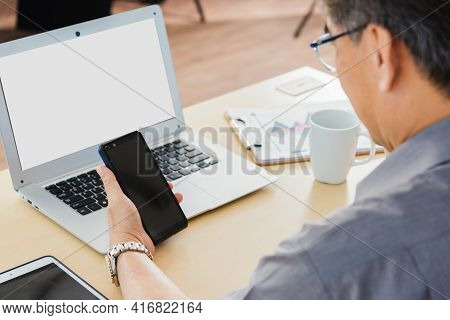 Old Businessman Using The Mobile Phone To Video Call Conference On Desk Table At Office. Asian Senio