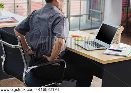 Asian Hard Senior Businessman Working With Laptop Computer Has A Problem With Back Pain. Old Man Fee