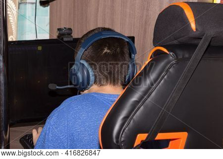 Teenager In Blue Headphones Behind The Monitor. A Boy With Headphones Studies At Home. Homeschooling