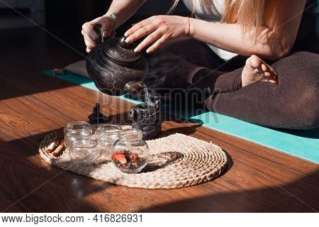 Woman Sitting In Lotus Position, Making Herbal Tea, Close-up. Tea Ceremony In The Yoga And Meditatio