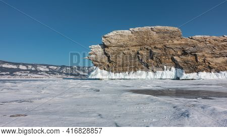 A Picturesque Rocky Island Rises Above An Icy Lake Against A Blue Sky. A Rock With Bizarre Outlines,