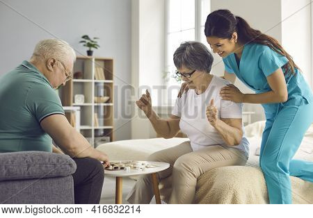 Supportive Care Giver Watching Couple Of Her Happy Senior Patients Play Checkers