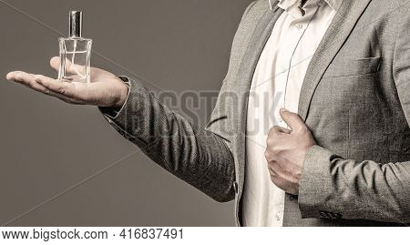 Man In Formal Suit, Bottle Of Perfume, Closeup. Fragrance Smell. Men Perfumes. Fashion Cologne Bottl