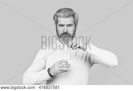 Male Taking A Pill With A Glass Of Water. Man Take Some Pills, Holds Glass Of Water, Isolated On Blu