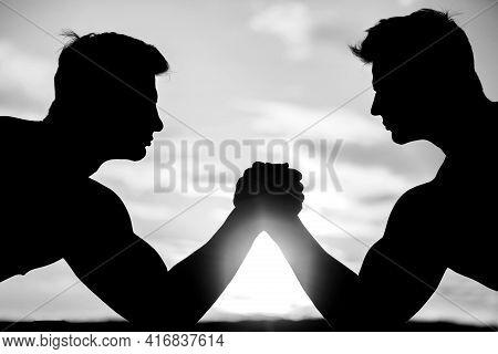 Two Men Arm Wrestling. Rivalry, Vs, Challenge, Strength Comparison. Sunset, Sunrise.
