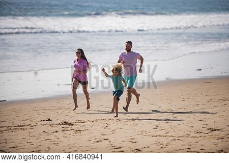 Sporty Family Running Out The Water In Beach. Summer Vacations And Sporty Healthy Family. Father, Mo