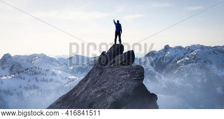 Composite. Adventurous Man Hiker On Top Of A Steep Rocky Cliff. Over The Puffy Clouds. Sunset Or Sun