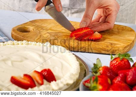 Woman Baker Cuts Strawberries For Strawberry Cake. Homemade Strawberries Cake Made From Meringue Cak