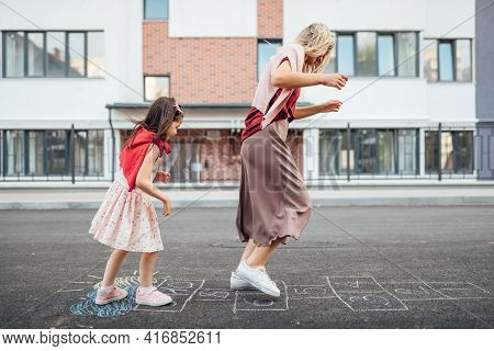 Side View Of A Joyful Little Girl Playing Hopscotch With Her Mother On Playground Outdoors. A Child