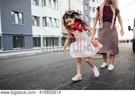 Happy Little Girl Playing Hopscotch With Her Mother On Playground Outdoors. A Child Plays With Her M