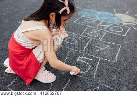 A Cute Little Girl Drawing With Chalk Hopscotch On The Playground. Child Playing The Game Outside. T