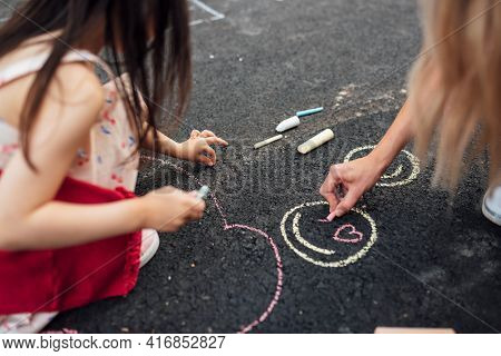 Closeup Of Little Girl Drawing With Colorful Chalks On The Playground. Child Playing With Her Mom Th