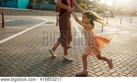 Image Of A Pretty Little Girl Dancing Together With Her Mother In Sunlight Outside. Cute Daughter Pl