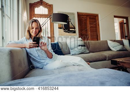 Caucasian Female Typing On Cellular Device Relaxing On Couch