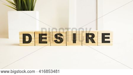 Wooden Cubes With Letters On A White Table. The Word Is Desire. White Background.