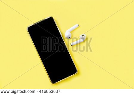 Smartphone With Blank Screen  With Earphones On Yellow Paper Background Top View. Concept Listen To