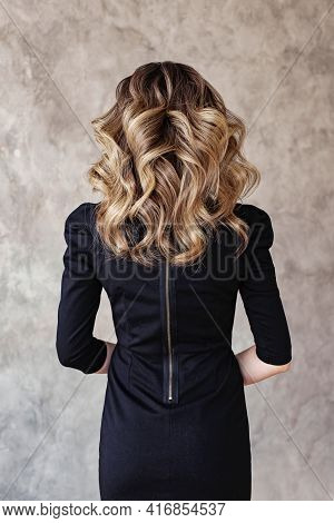 Beautiful Woman Back With Curly Hairdo On Gray Background