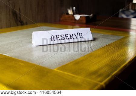 The Flying Around The Plate Is Reserved, Which Stands On The Wooden Table In The Restaurant. Reserva