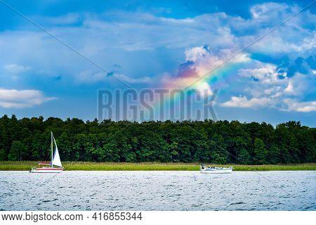 Yacht With White Sail On A Lake Against Gloomy Rainy Blue Sky And The Rainbow. Summer Sailing Vacati