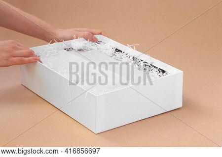 A Womans Hands Pack For A Customer A White Box With Clothes In White Tissue Paper And Shredded Paper