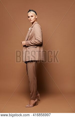 Gorgeous Woman With Blond Hair In A Stylish Suit Posing Against A Beige Background. Blond Female Mod