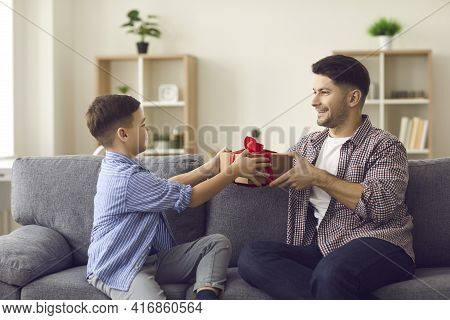 Cute Boy Gives Congratulations To His Dad On The Holiday And Gives Him A Gift Box.