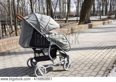 Baby Stroller With Baby In The Park Outdoors.