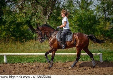 A Girl Rider Trains Riding A Horse On A Spring Day.