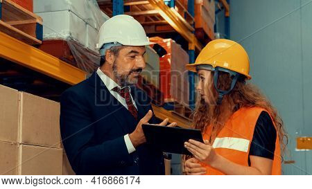 Warehouse Senior Manager Discuss With Worker In The Storehouse . Logistics , Supply Chain And Wareho