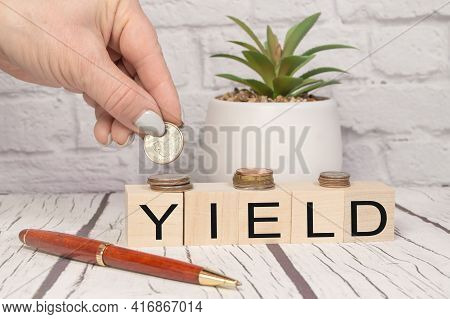 Yield A Word On Wooden Dice And Coins In Your Hand On A Wooden Table. Harvest Profit Business Concep