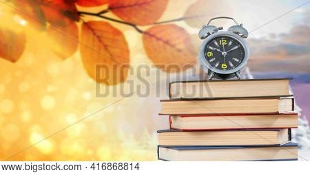 An alarm clock standing on top of a stack of books. autumn leaves and winter landscape in the background. back to school concept.