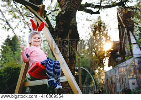 Happy Beautiful Little Toddler Girl With Red Easter Bunny Ears Having Fun On Swing In Domestic Garde