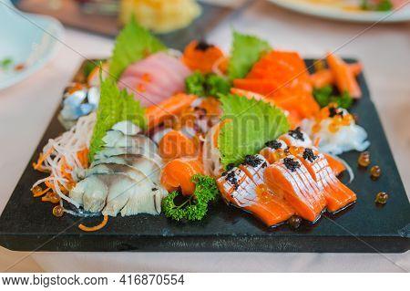 Mixed Sliced Fish Sashimi On Ice In Black Bowl. Sashimi Salmon Tuna Hamachi Prawn And Surf Calm Set,