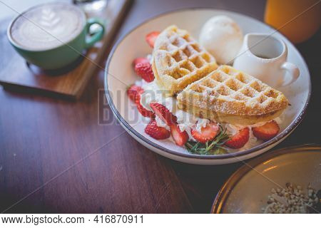 Picture Of Waffle Pancake Desert With Vanilla Ice Cream, Fresh Strawberry And Honey Syrup