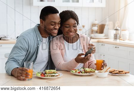 Romantic African American Spouses Checking New App On Smartphone During Breakfast