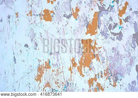 Texture background,peeling light stucco and peeling brown paint with turquoise streaks on the wall surface.Texture background.Texture background of peeling paint,light peeling paint on the concrete surface,close up of peeling paint texture on the old conc