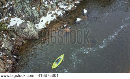 paddling inflatable whitewater kayak on a mountain river (Poudre River in Colorado), aerial perspective in early spring with some snow