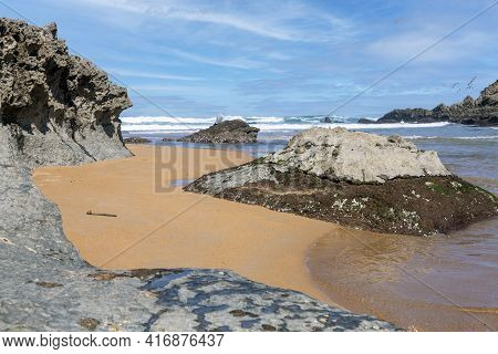 Quiet And Lonely Place Next To A Mixed Beach Of Sand And Rocks In The Cantabrian Sea With Waves And