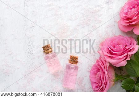 Two bottles with rose oil, crystals of mineral bath salts and pink roses on the white  wooden table.