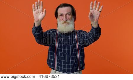 Happy Friendly Elderly Bearded Man Waves Hand Palms In Hello Gesture Welcomes Someone With Hospitabl