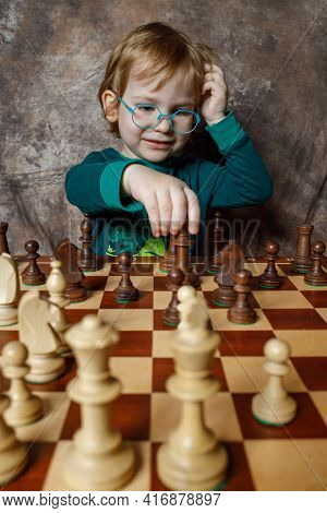 A Little Boy Is Playing Chess.chess Tournament.