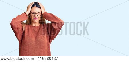 Beautiful young woman wearing casual clothes and glasses suffering from headache desperate and stressed because pain and migraine. hands on head.