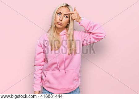 Young blonde woman wearing casual sweatshirt pointing unhappy to pimple on forehead, ugly infection of blackhead. acne and skin problem