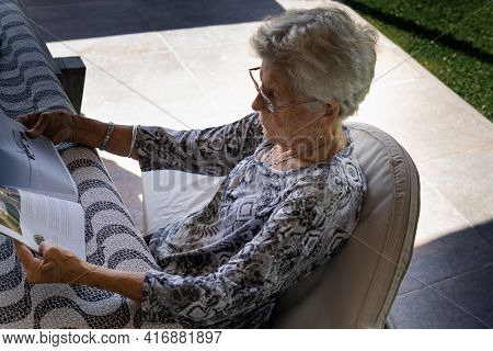 Gray-haired And Short-haired Old Woman With Glasses. The Woman Is Alone. The Elderly Lady Is Sitting