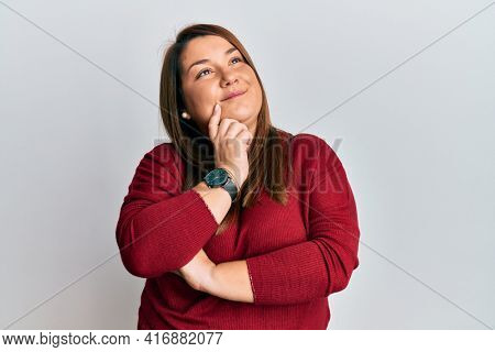 Beautiful brunette plus size woman wearing casual clothes thinking concentrated about doubt with finger on chin and looking up wondering