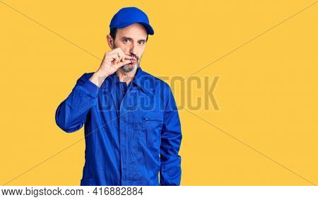 Middle age handsome man wearing mechanic uniform mouth and lips shut as zip with fingers. secret and silent, taboo talking